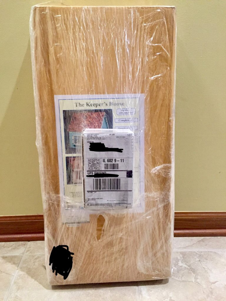 The wrapped up package that contains the Keeper's House dollhouse kit. It's covered in plastic wrap.