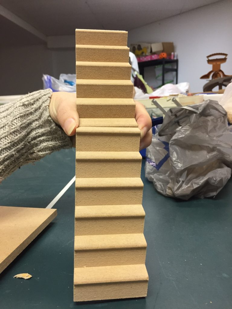A picture of the two stair pieces standing up while I hold them. It looks like a functioning staircase from the front view. Also, I have a messy basement which you can see in the background.