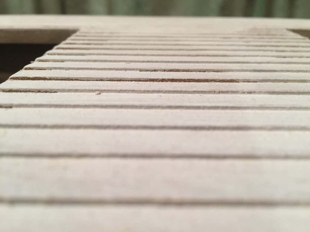 A picture of the underside of the clapboard siding. There's dirt and debris stuck in the grooves.