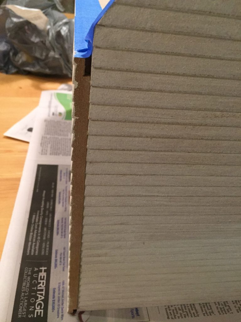 A picture of an raw edge of wood on the dollhouse. It's not primed.