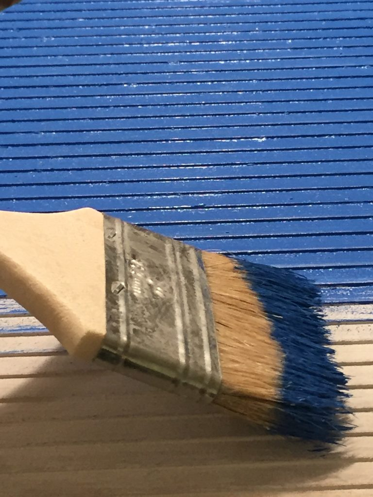 A picture of the paint brush going in the direction of the clapboard, side to side.