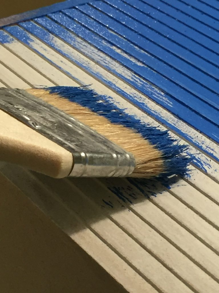 A picture of the paint brush pointing up and down to make it easier to poke under the clapboard grooves
