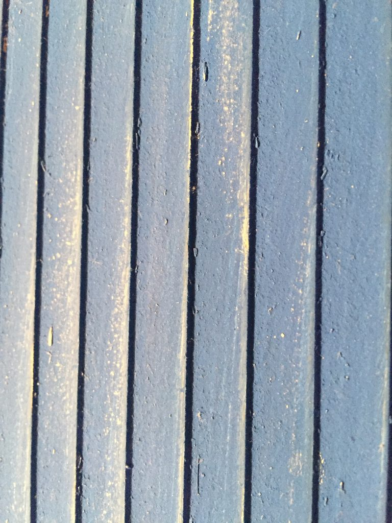 A close up picture of the clapboard after I sanded it. The paint is coming off.