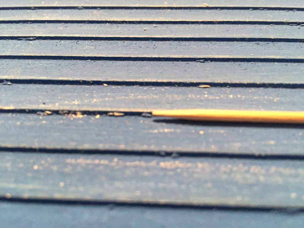 A close up picture of the wood bits and fuzz under the clapboard.