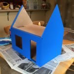 The side view of a half-painted dollhouse