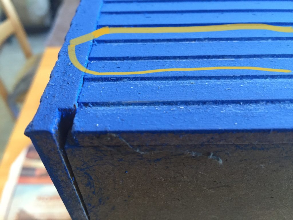 A close up picture of the dollhouse clapboard siding I sanded with an emery board circled in yellow.