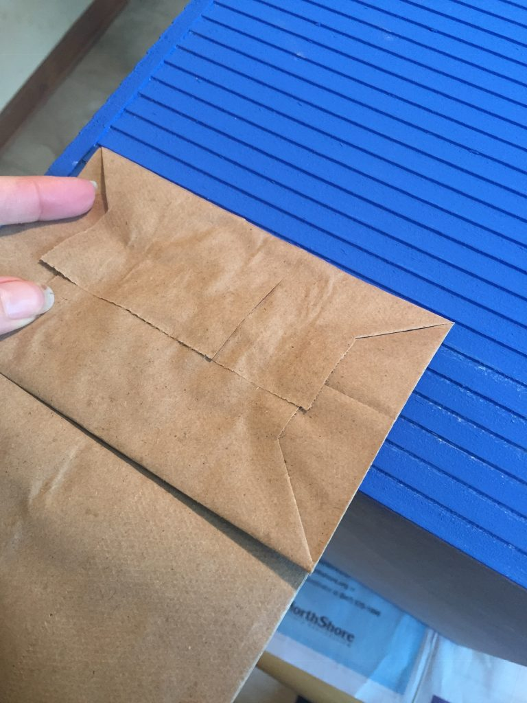 A picture of the bag lined up with the grooves for the dollhouse clapboard siding for sanding.