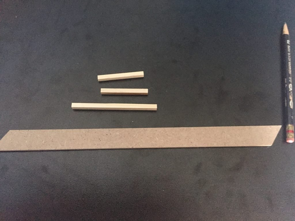 A picture of the four pieces I have leftover once I finished identifying the other parts. There's one long, flat strip, and three sticks