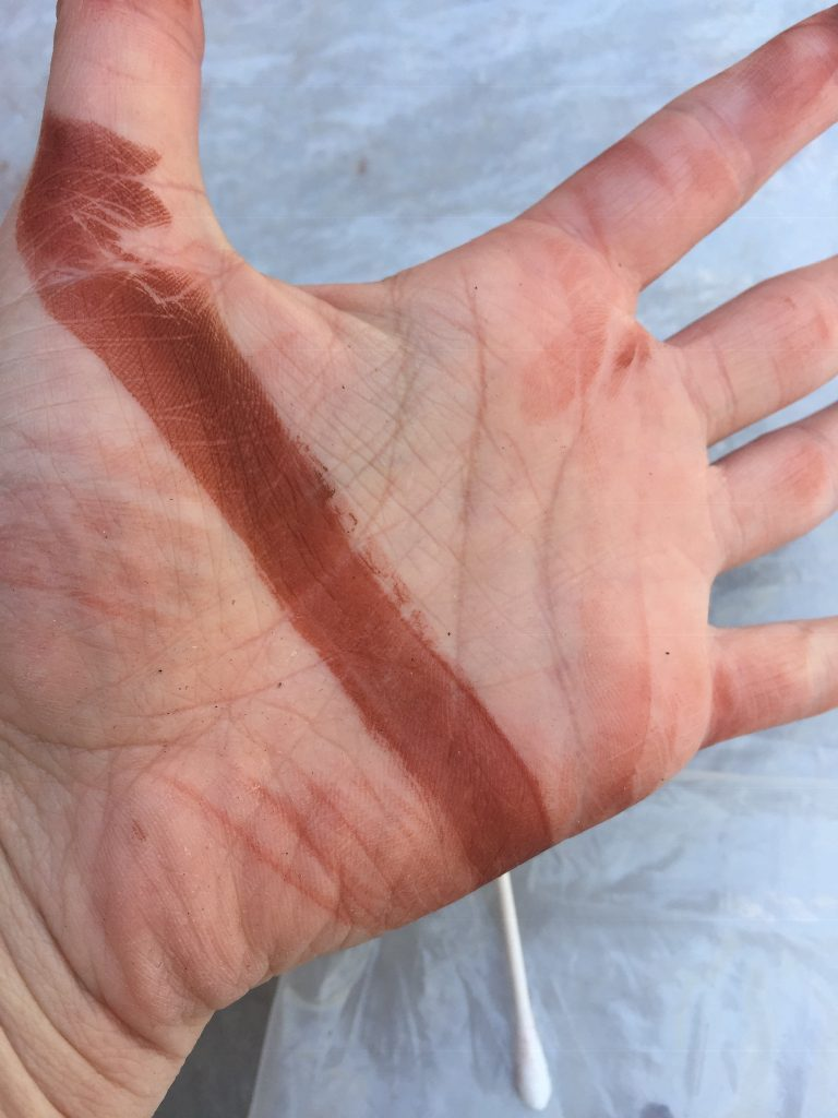A picture of my hand with a long brown stain on it after learning how to batch dye dollhouse shingles