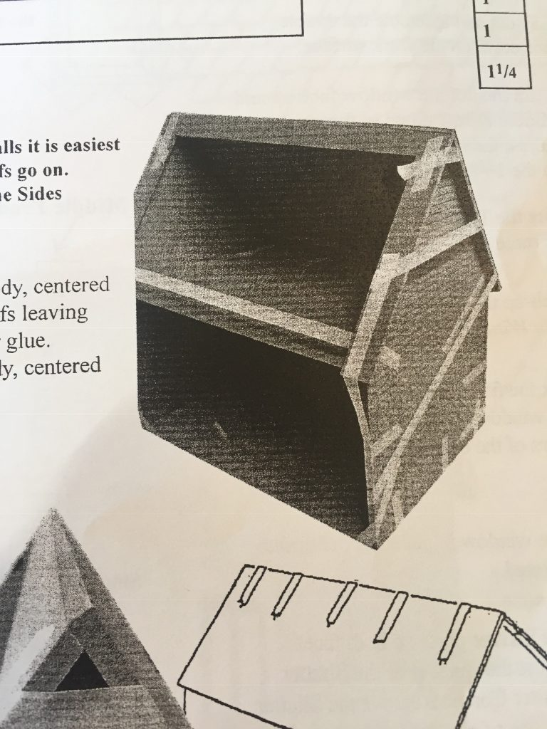 A picture from the instruction book with the house taped together after the roof is on. There's a lot of tape.