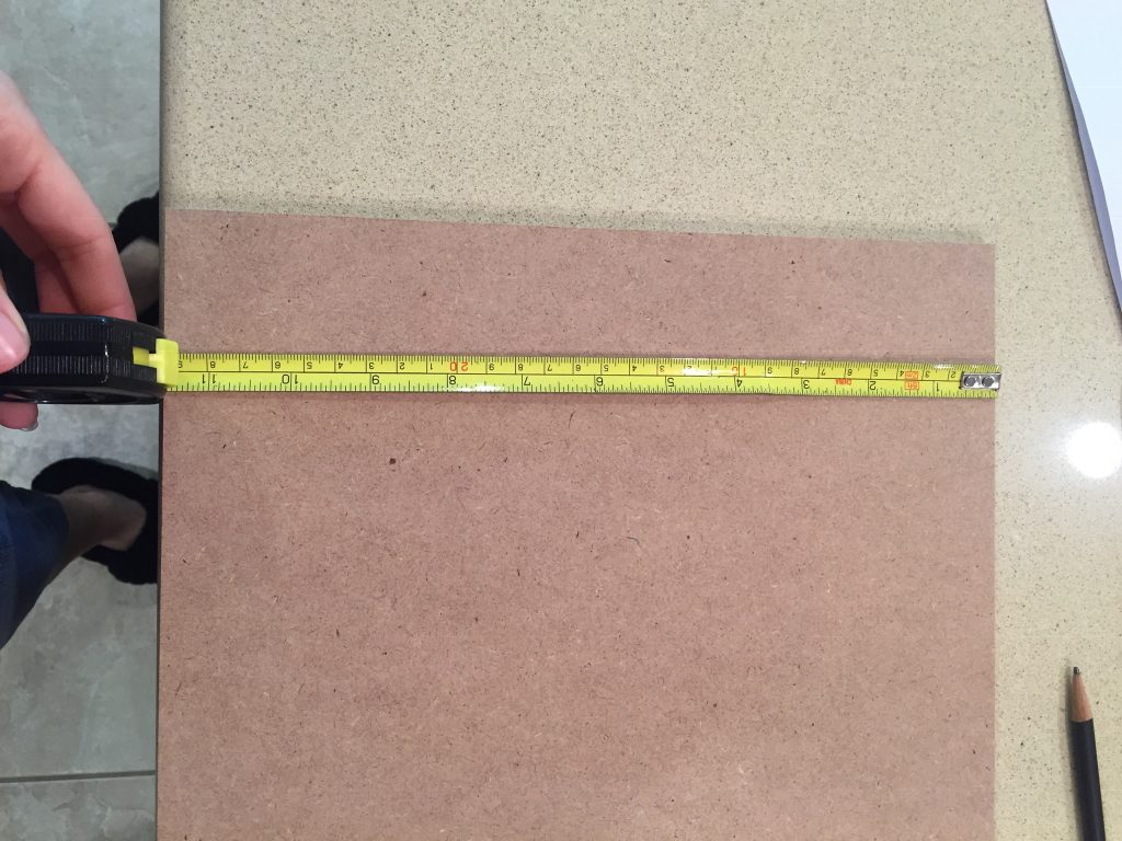 A picture of the tape measure hooked to the dollhouse roof piece