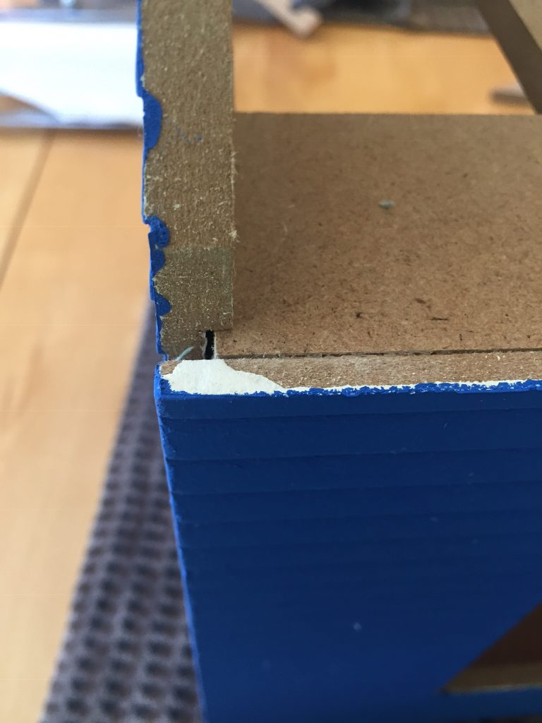 A picture of the dollhouse clapboard after I took the painter's tape off. There's paint in the grooves