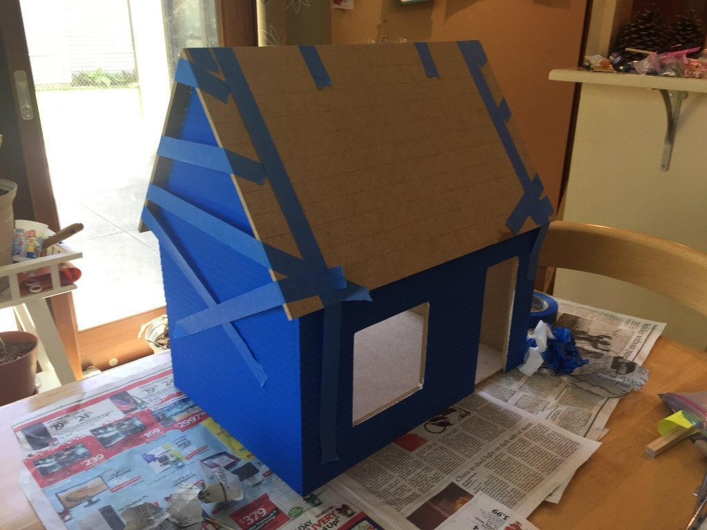 The dollhouse roof taped on within an inch of its life.