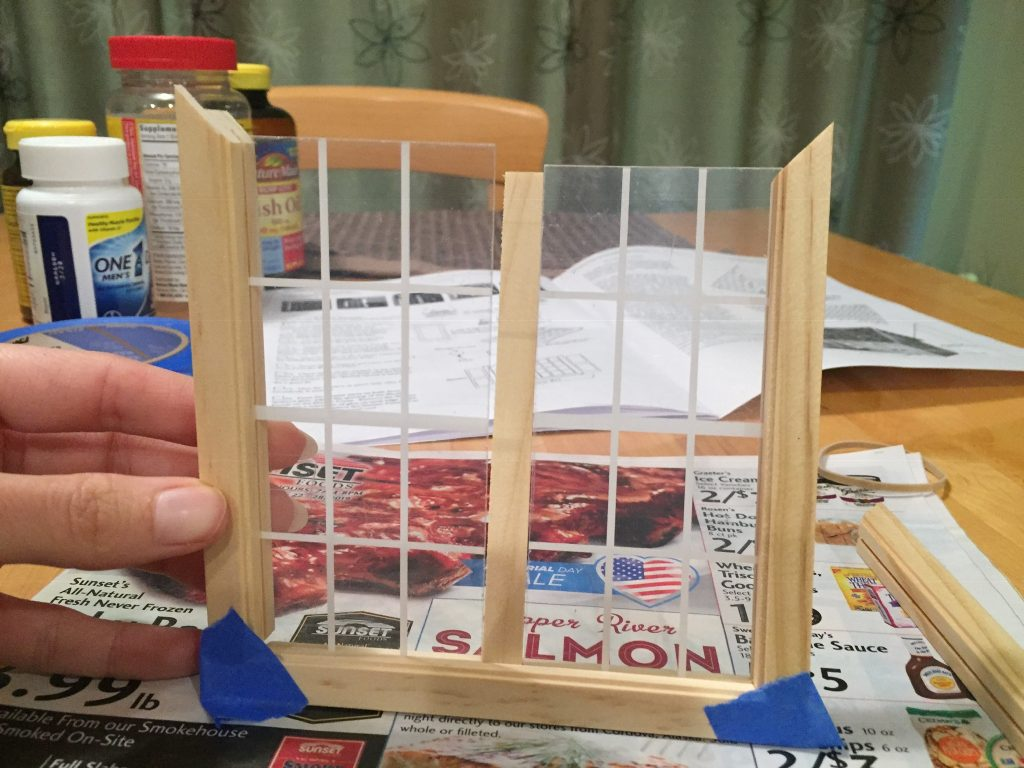 A picture of me holding the mostly assembled window frame on its side to get the fourth side on.