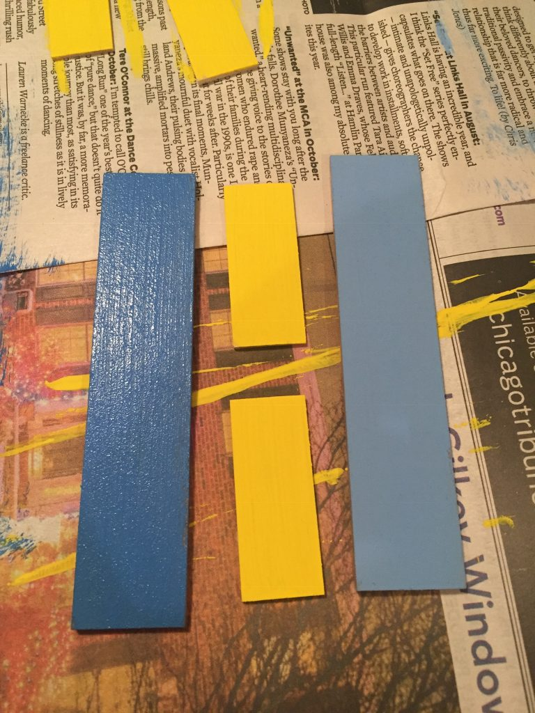 A picture of the small yellow shutter pieces between the two large, blue shutter pieces.