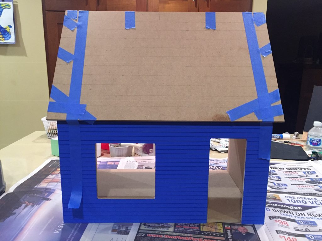 A picture of the dollhouse with the roof glued on and still taped up