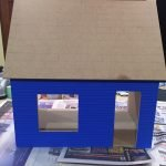 A picture of the dollhouse with the roof glued on after the tape is off