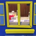 A close up picture of the window frame, shutters and window box dry fit on the house.