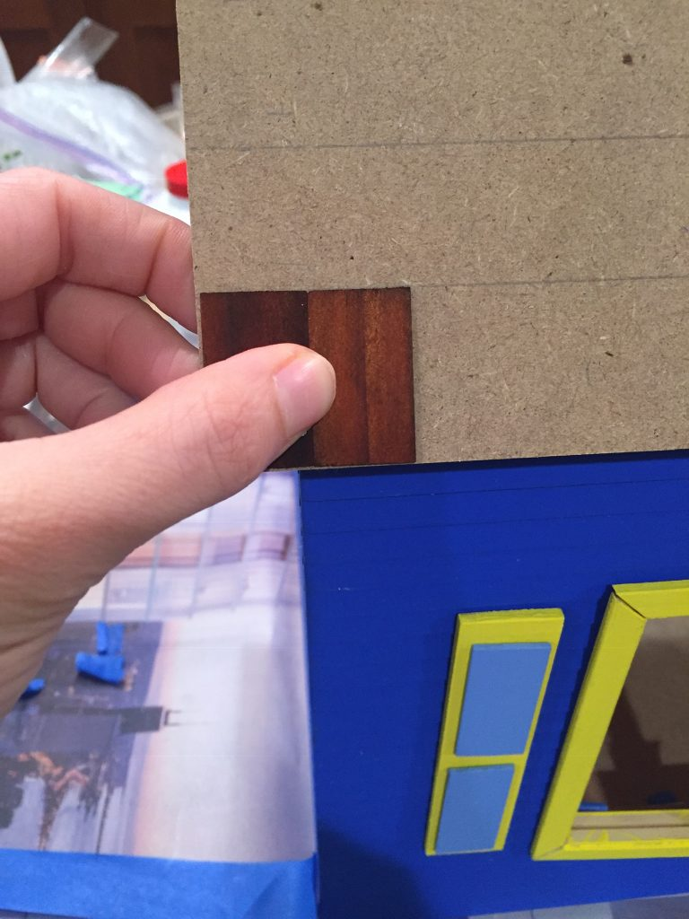 A picture of me holding two shingles on the roof of the dollhouse