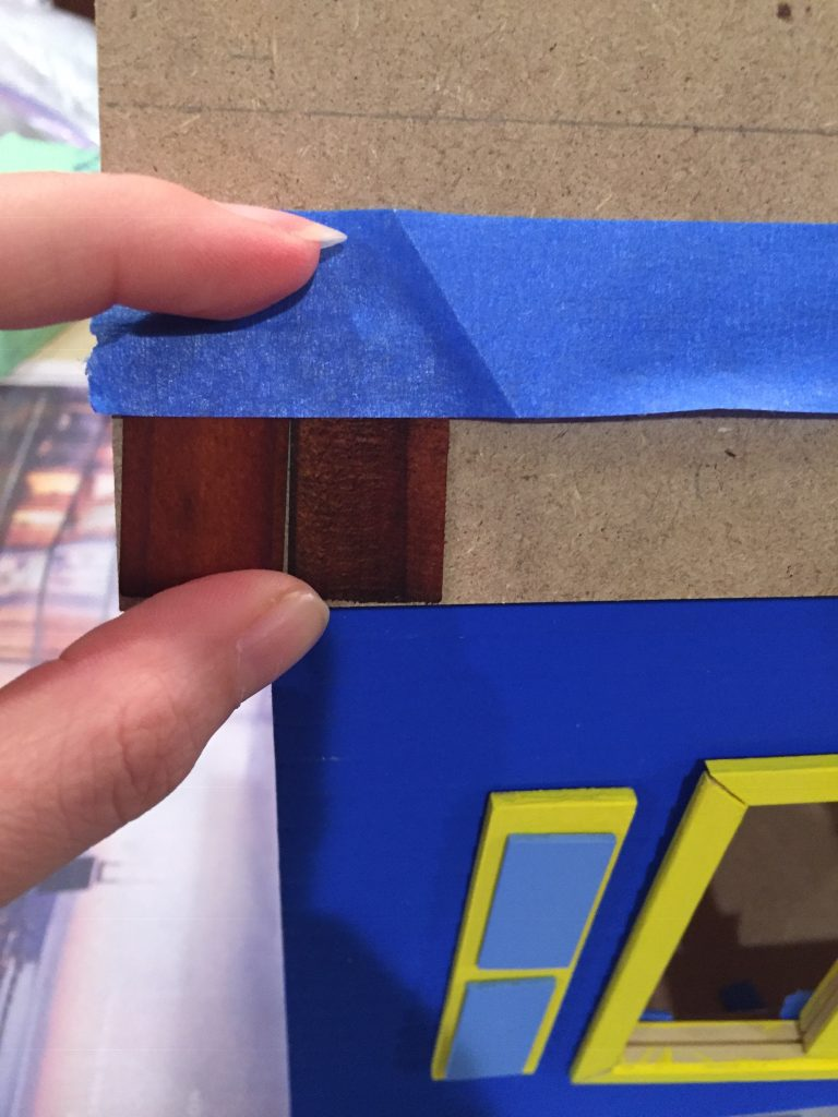 A picture of me taping two shingles to the dollhouse roof