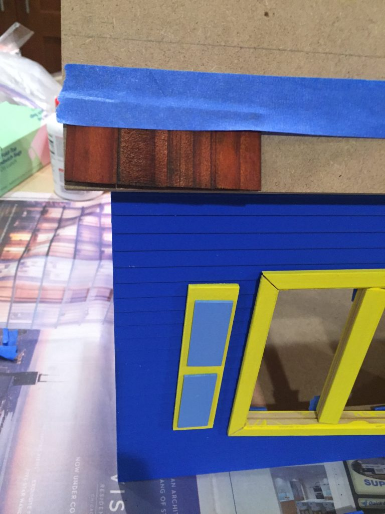 A picture of four shingles taped to the dollhouse roof