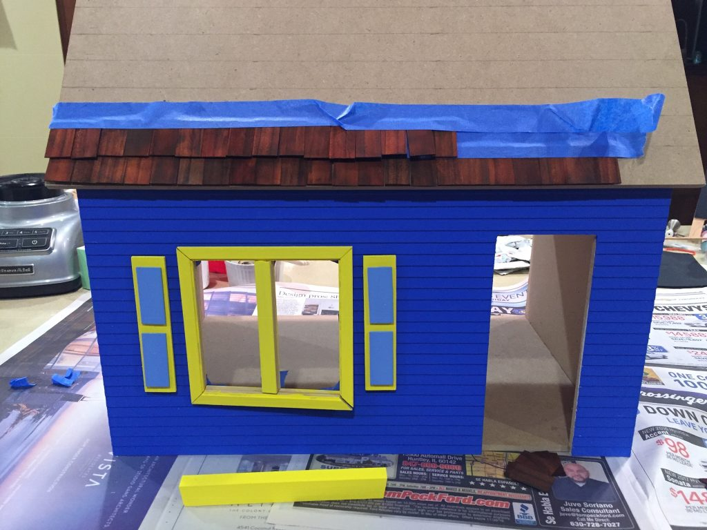 A picture of two rows of shingles taped to the dollhouse roof