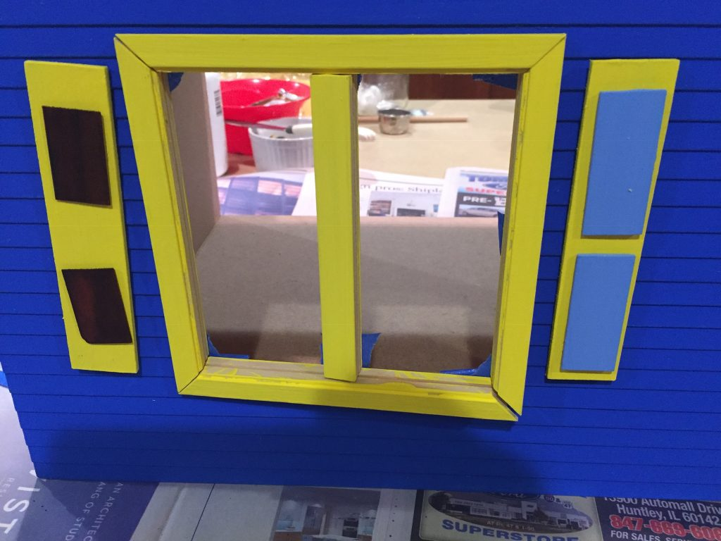 A picture of the shutters with the dollhouse shingle accents next to the completed window on the dollhouse