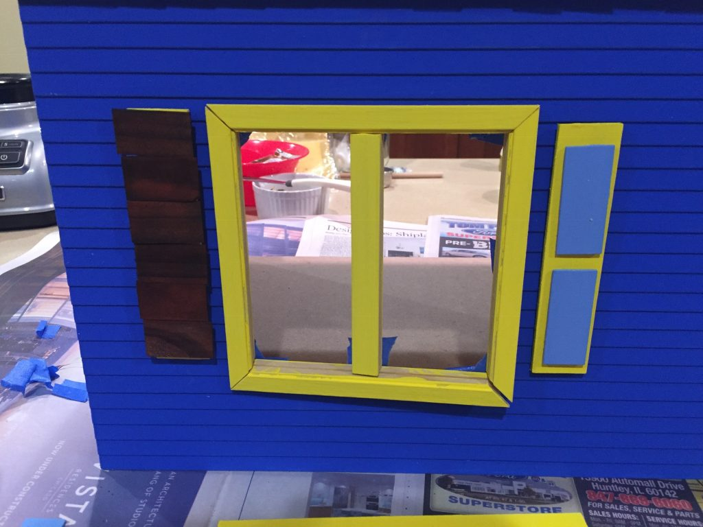 A picture of the shingle covered shutter on the dollhouse.