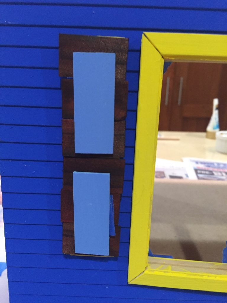 A close up picture of the shingle covered shutter with the blue accent pieces on the dollhouse.
