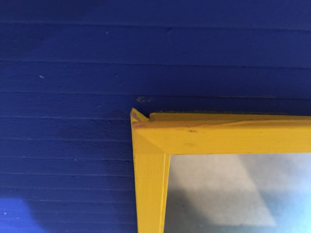 A picture of the dollhouse window frame still not fitting in the opening.