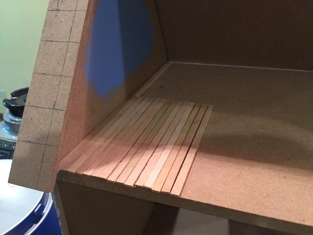A picture of the balsa wood planks laid out from front to back on the upper floor of the dollhouse.