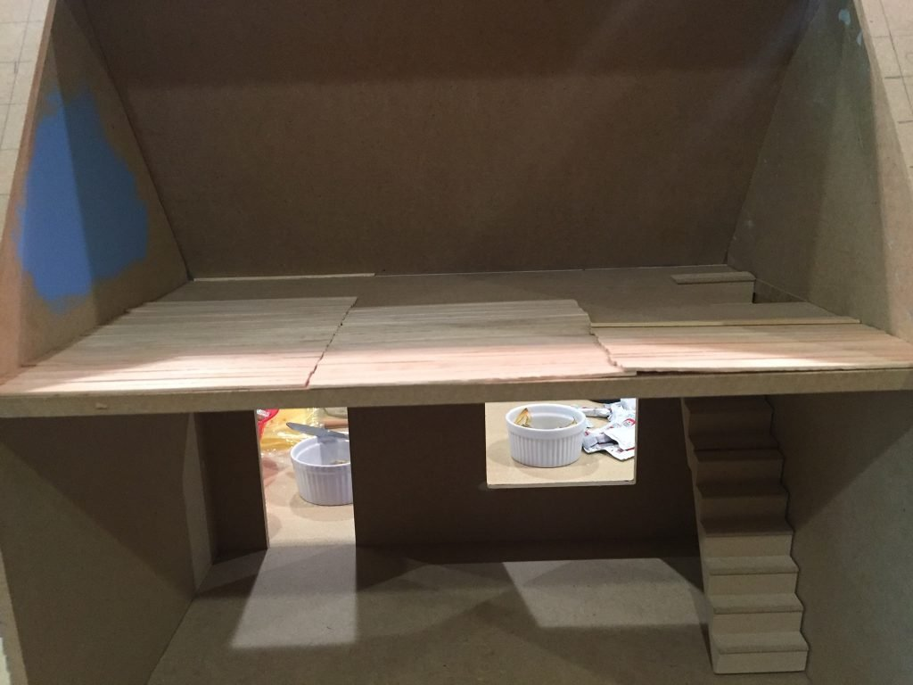 A picture of the balsa wood planks laid out on the top floor of the dollhouse going from side to side (left to right).