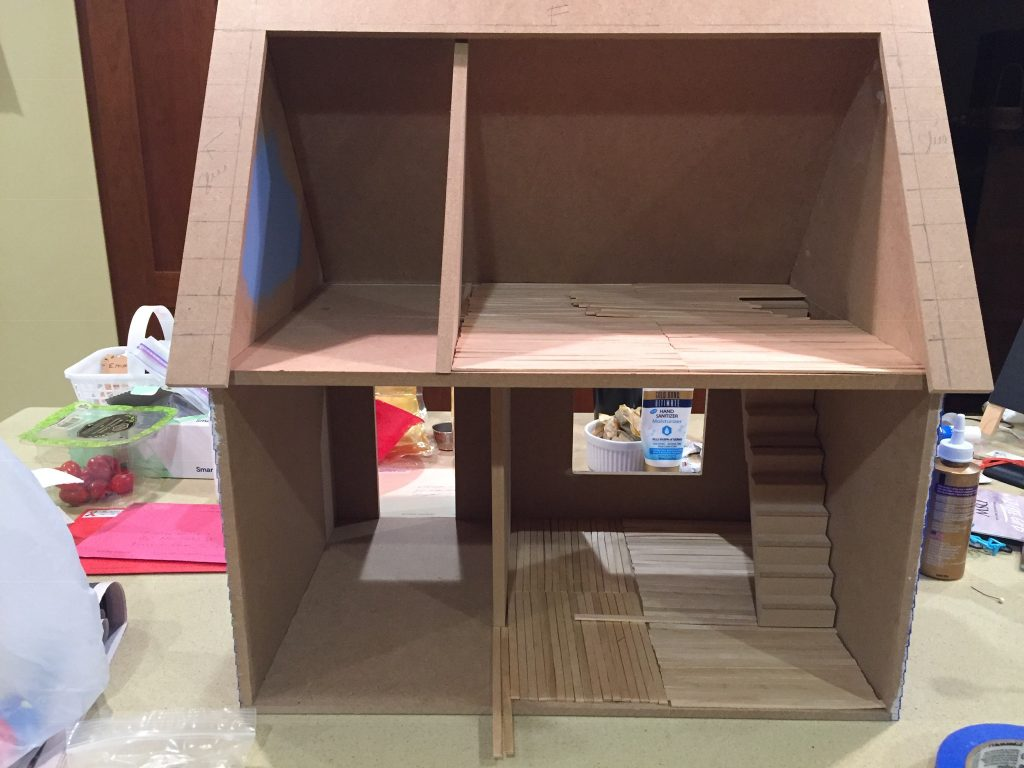 A picture of the dollhouse with the room dividers in place and the balsa wood strips laid out.