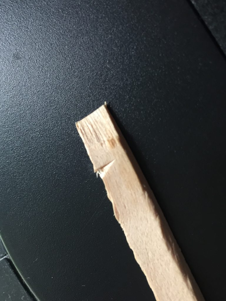A picture of the balsa wood stick after I forced the scissors to cut it. The edge is uneven and splintered.