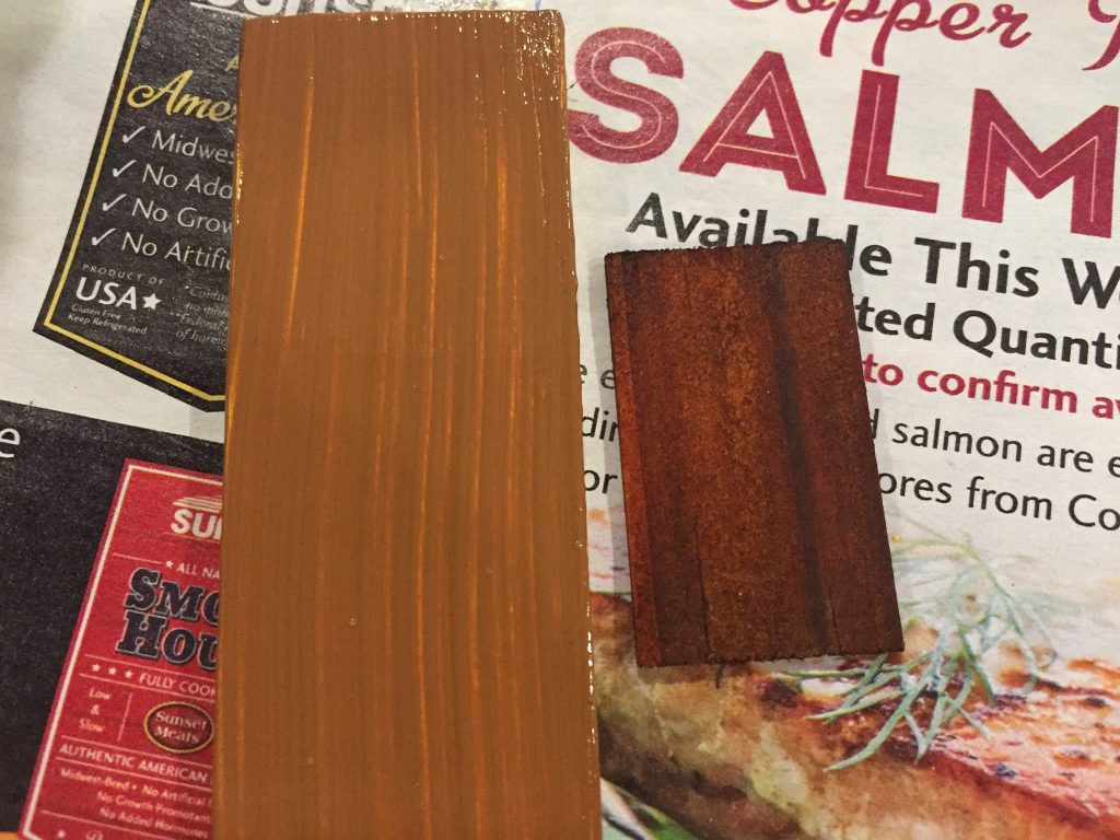 A picture of the large shutter piece with three coats of brown paint next to the dollhouse shingle for color comparison