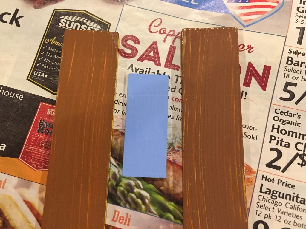 A picture of the two shutters in both browns with the blue accent piece between them.