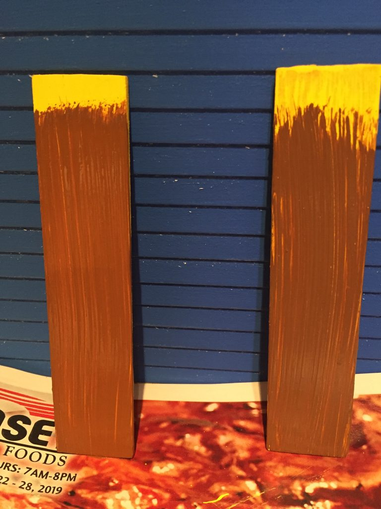 A picture of the two painted shutter pieces side by side against the house.