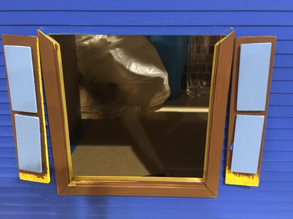 A picture of the shutters and most of the window frame dry fit onto the dollhouse.