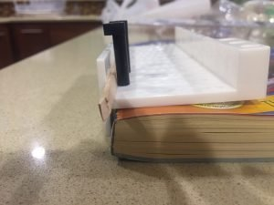 A close up of the miter box on the phone book with the balsa wood strip hanging out of the edge of the miter box