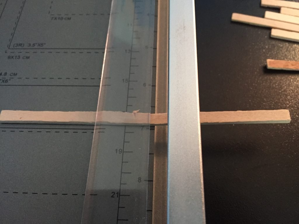 A picture of the balsa wood strip under the paper guide of the paper cutter.