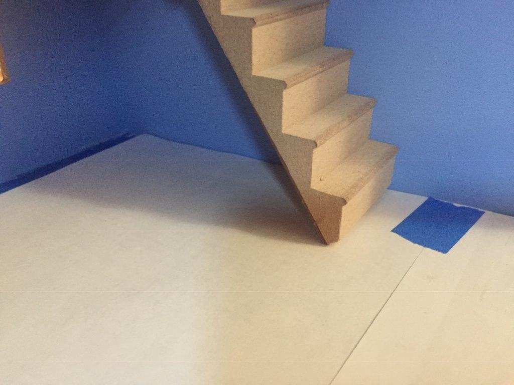 A picture of the stairs where they meet the dollhouse floor.