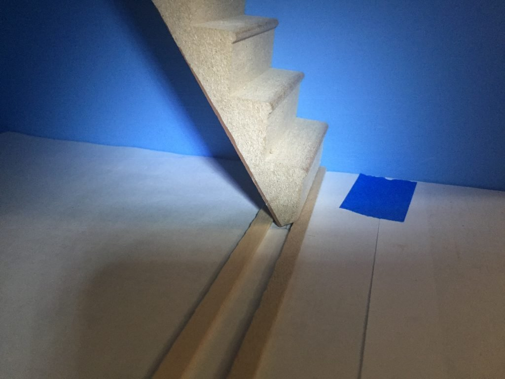 A picture of the stairs with a balsa wood strip on either side of the bottom stair.