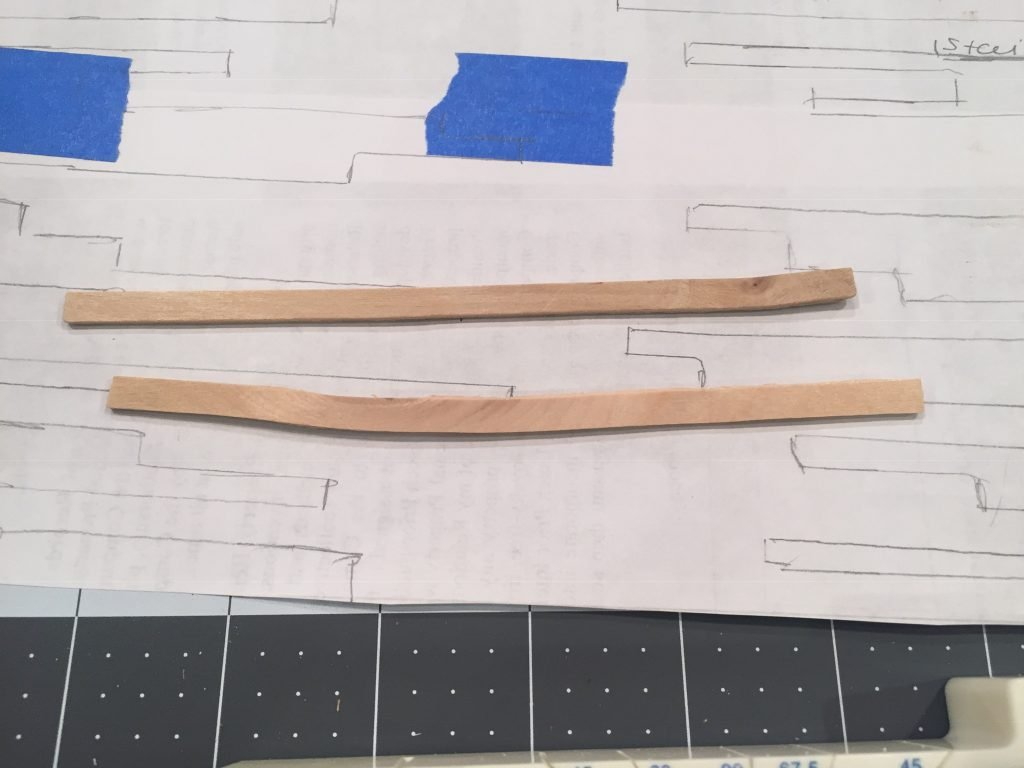 A close up picture of two balsa wood strips showing that they aren't perfectly straight.