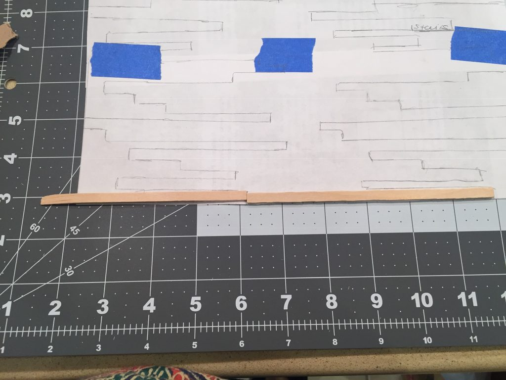 A picture of two balsa wood strips on the template so I can figure out where to cut.