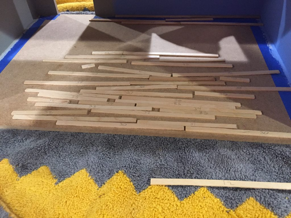 A picture of the balsa wood strips on the floor of the dollhouse. They're kind of in place, kind of not.