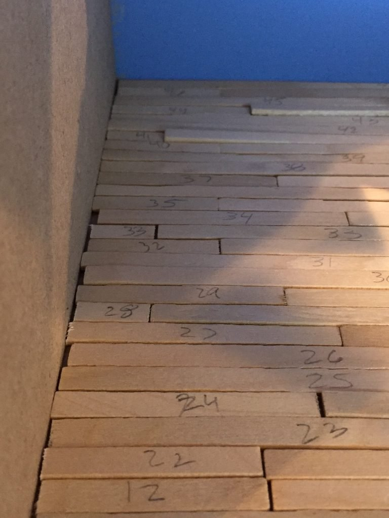 A close up the balsa wood floor against the interior wall. It doesn't line up right.