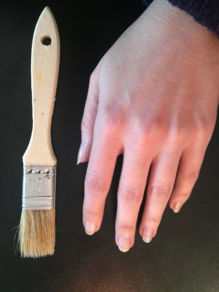 A picture of my hand next a paintbrush