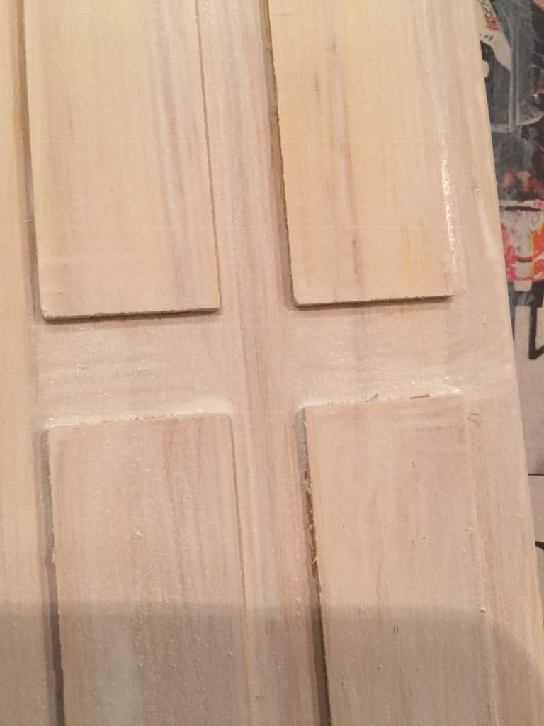 A closeup view of the center of the door and raised panels. The paint has gathered near the raised edges.