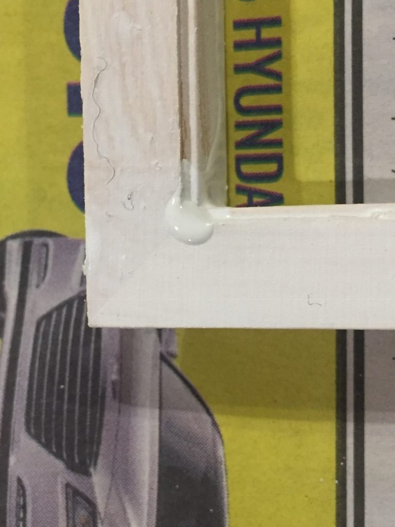 A close up of the door frame after the primer dried. There's fuzz stuck in it and a pool of dried paint on the corner.