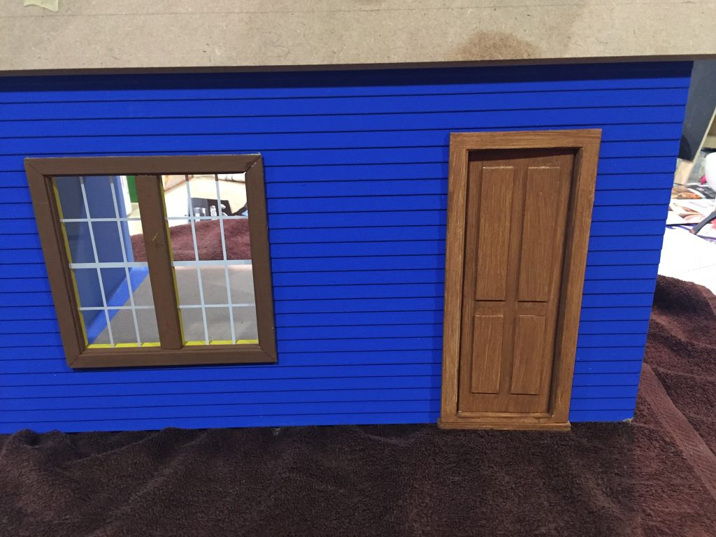 A picture of the door and window in the dollhouse